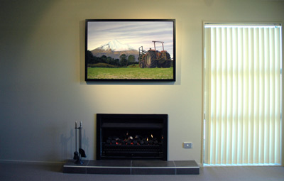 The original, 'Tractor with Mountain' by Grant McSherry is a large size oil painting, finished in a hand crafted, black lacquer shadow frame with negative space.